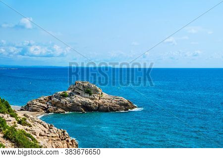 view of Illot del Torn, a rock formation topped by the remains of an old watchtower, in the Torn Beach, in Hospitalet del Infant, Spain