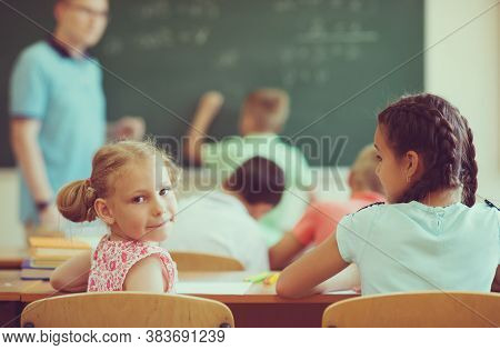 Young Male Teacher Explaining Math At The Blackboard During A Lesson At Primary School