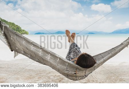 Woman Relaxing In The Hammock With Her Feet Up In Tropical Beach On Summer Vacation.