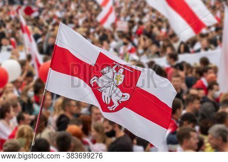 National white red white flag of Belarus with historic belarusian coat of arms Pahonia. Blurred crowd of people protesting after 2020 presidential elections. Belarus White-red-white flag