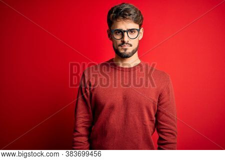 Young handsome man with beard wearing glasses and sweater standing over red background Relaxed with serious expression on face. Simple and natural looking at the camera.