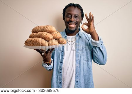 Young african american man holding tray with healthy wholemeal bread over white background doing ok sign with fingers, excellent symbol