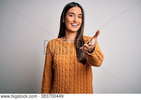 Young beautiful brunette woman wearing casual sweater over isolated white background smiling friendly offering handshake as greeting and welcoming. Successful business.