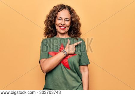 Middle age beautiful woman wearing t-shirt with red star revolutionary symbol of communism smiling cheerful pointing with hand and finger up to the side
