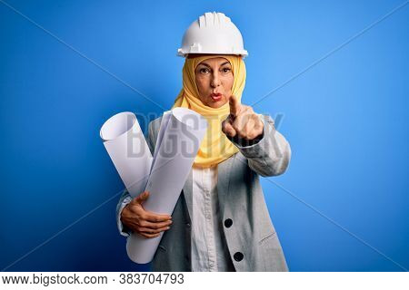 Middle age architect woman wearing muslim hijab and security helmet holding blueprints pointing with finger to the camera and to you, hand sign, positive and confident gesture from the front