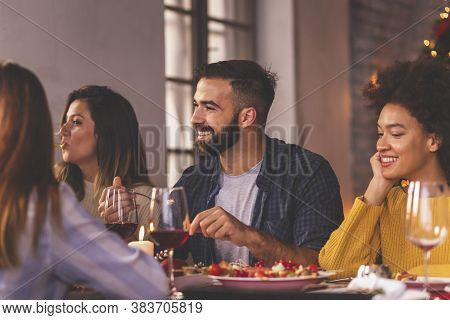 Group Of Friends Having A Pleasant Conversation During Christmas Dinner; Friends Celebrating Thanksg