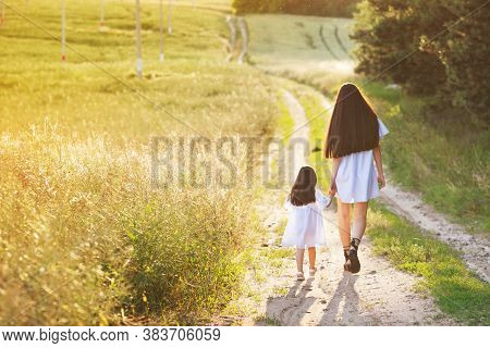 Happy Family Concept. Mom And Baby Holding Hands And Walking In Evening In Park In Rays Of Beautiful