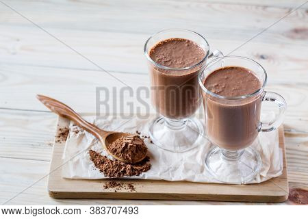 Coffee Latte Macchiato Or Hot Chocolate In Two Glasses On Wooden Background, A Spoon With Cocoa Powd