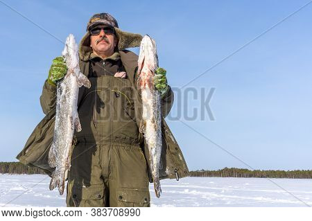 Winter Fishing A Fisherman Catches Fish In Winter. Winter Sport