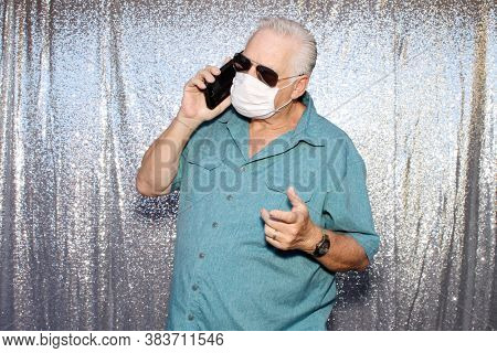 Photo Booth. A  Caucasian Man wears a Anti-Covid 19 Face Mask as he talks on his phone and poses for photos in a Photo Booth with a silver sequin background.