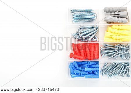 Screws And Dowels Of Various Sizes, Types And Colors In A Transparent Plastic Box.
