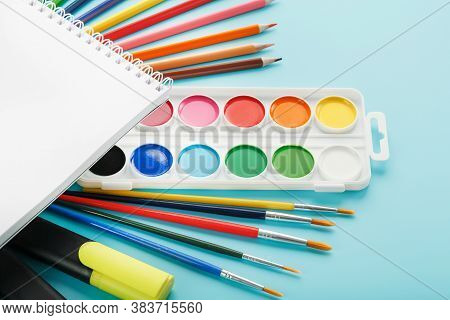 An Album Of Brushes And Paints With School Supplies On A Blue Background. Album, A Place To Copy Spa