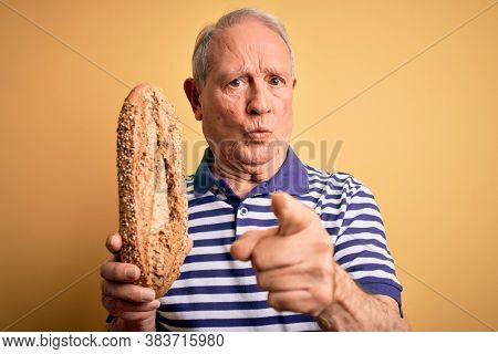 Grey haired senior man holding healthy wholemeal bread over yellow isolated background pointing with finger to the camera and to you, hand sign, positive and confident gesture from the front
