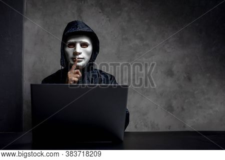 Hacker Wearing A White Mask In Front Of His Computer. Hacker Hacks Network, Space For Text.