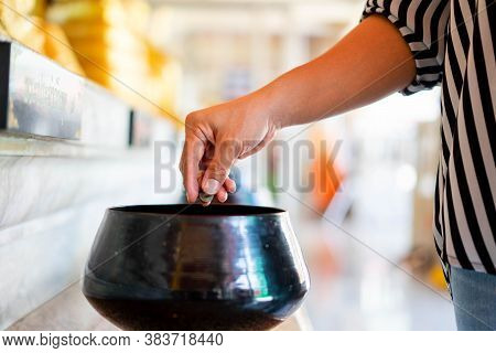 A Hand Putting Coins In One Of Monk Alms Bowl For Merit In Buddhism With Lots Of Monk Alms Bowls Bes