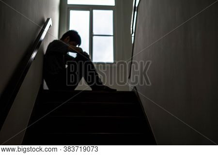 Blurred Photo Of A Sad Young Man Sitting At The Stairs In The Dark, The Sun Is In Sorrow, Life Probl