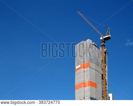 Orange Tower Cranes At Top Of Condominium Structure Covered With Gray Canvas With Clear Blue Sky And