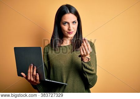 Young brunette woman with blue eyes working using computer laptop over yellow background doing money gesture with hands, asking for salary payment, millionaire business