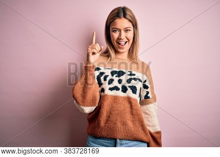 Young beautiful blonde woman wearing fashion animal print sweater over pink background pointing finger up with successful idea. Exited and happy. Number one.