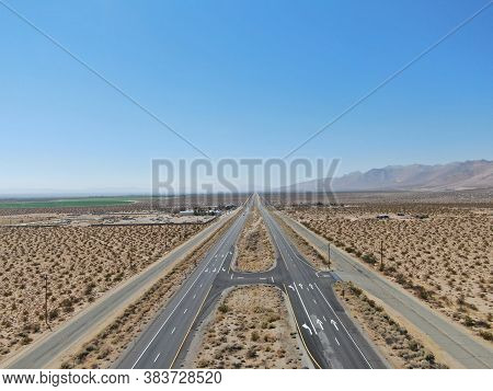 Aerial View Of Road In The Middle Of The Desert Under Blue Sky In Californias Mojave Desert, Near Ri