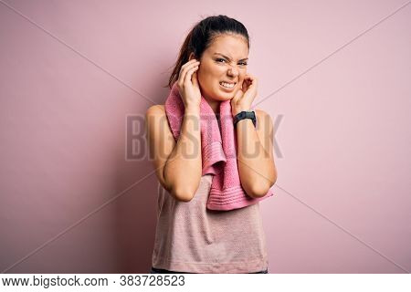 Young beautiful brunette sportswoman wearing sportswear and towel over pink background covering ears with fingers with annoyed expression for the noise of loud music. Deaf concept.