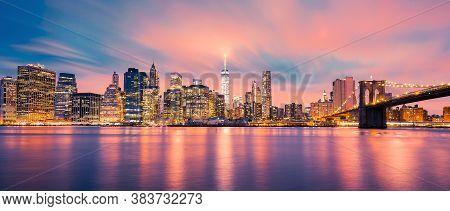 View Of New York City Manhattan Midtown At Dusk With Skyscrapers Illuminated Over East River