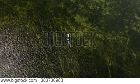 Aerial Image Of Motorboat Floating In Black Sea Water. The Sandy Bottom Through The Clear Water