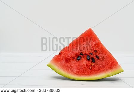 Close-up Of A Triangular Piece Of Watermelon On A Wooden Light Table And White Background. Ripe Juic