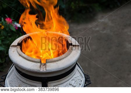Tandoor In The Garden At The Evening. Firewood Is Burned In A Tandoor Heating It Before Cooking Meat