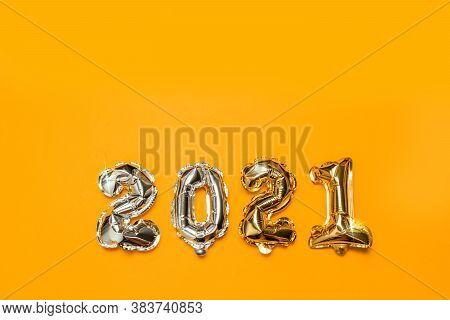 2021 Gold Foil Balloon Flying In The Air On A Yelllow Background. Concept Design For Christmas And N
