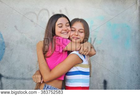 two girls hug each other affectionately