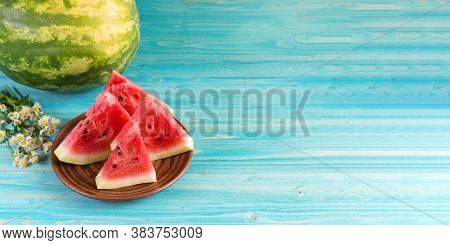 Four Slices Of Ripe Fresh Watermelon Lie In A Clay Plate On A Blue Wooden Table. Theres A Whole Wate