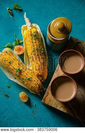 Top view of brewed hot milk tea with roasted grilled corn on blue background. Delicious Grilled Corncobs and Two Cups of Chai, an ideal Indian monsoon brunch good for boosting immunity and health.