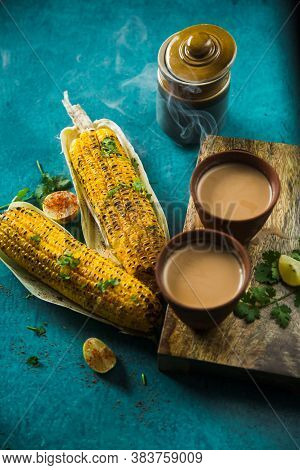 Top View Of Brewed Hot Milk Tea With Roasted Grilled Corn On Blue Background. Delicious Grilled Corn
