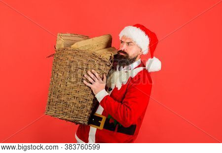 Santa Man. Winter Holiday. Basket Of Chopped Firewood. Bearded Man In Santa Claus Costume With Baske