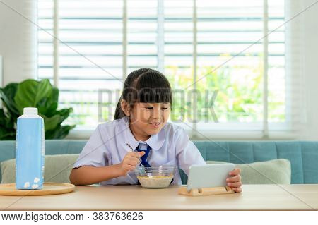Asian Elementary School Student Girl In Uniform Eating Breakfast Cereals With Milk And Looking Carto