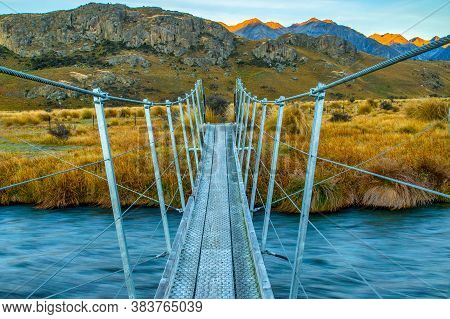 Swing Bridge Over An Alpine River With A View. This Was One Of The Locations For Lord Of The Rings M