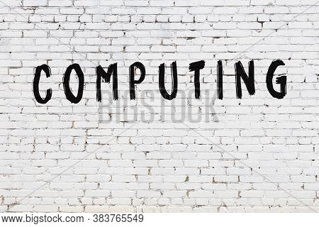 Inscription Computing Written With Black Paint On White Brick Wall.