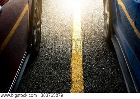Close Up Of Asphalt Road With Yelow Line. Beside With Two Car Race On The Road Fast Speed.