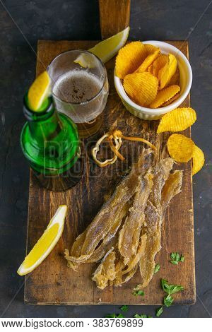 Silver Amber Fish With Pepper With Beer, Lemon And Potato Chips On Dark Wooden Board. Snack On Fish