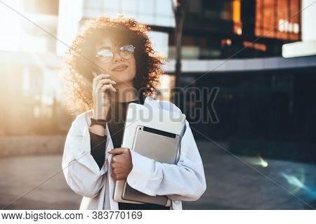 Young Curly Haired Businesswoman With Eyeglasses Embracing A Tablet And Posing Outside In The Sunshi