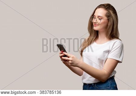 Mobile Chat. Online Communication. Happy Woman Reading Texting Message On Phone Isolated On Gray Emp