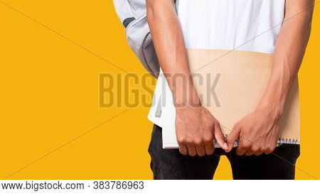 Student Lifestyle. Educational Courses. Unrecognizable Teenager Boy Holding Notebook Isolated On Ora
