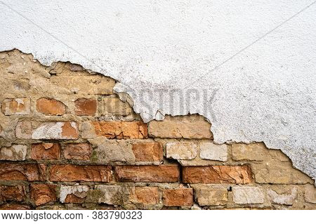 Chipped Plaster From The Wall And Visible Brickwork.