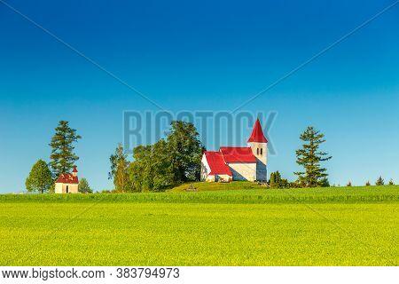 Rural Landscape With A Church In The Background. Saint Kosmas Church In Abramova Village, Turiec Reg