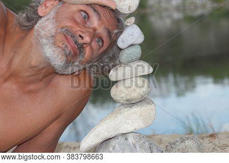 Mature Man Doing Stone Piles Along The River