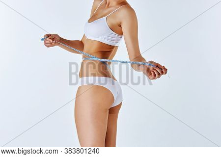 woman holding meter measuring perfect shape of her beautiful body