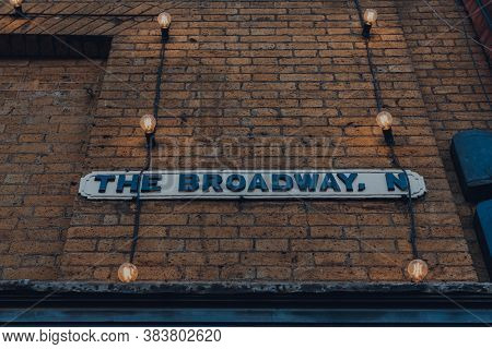 Street Name Sign Amongst A String Of Lights On The Broadway, Crouch End, London, Uk.