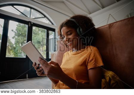Cheerful Young Woman Sitting On Floor With Backrest On Couch Using Digital Tablet And Headphone