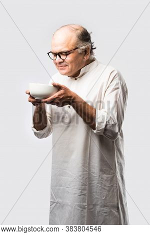 Expressive Indian Old Man Eating Food From Empty Or Blank White Plate Or Bowl